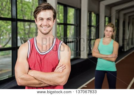 Portrait of man and woman standing with arms crossed in gym