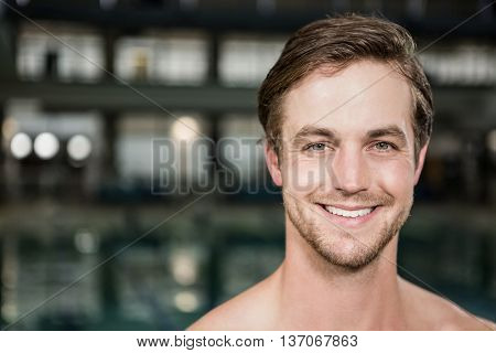 Portrait of happy swimmer standing near pool at the leisure center