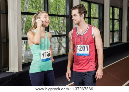 Happy man and woman listening to music and using phone at gym