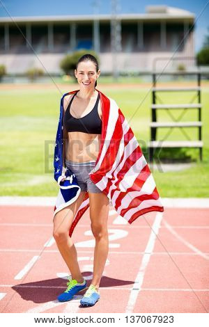 Portrait of female athlete wrapped in american flag on running track
