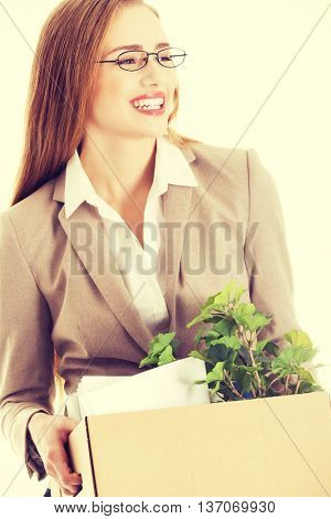 Businesswoman holding box with office items.