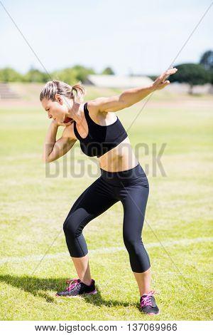 Female athlete preparing to throw shot put ball in stadium