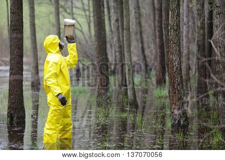 technician examining sample of water in floods area