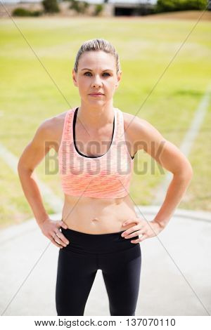 Portrait of female athlete standing with hands on hips in stadium