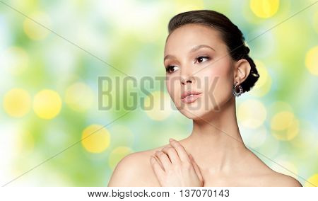 beauty, jewelry, accessories, people and luxury concept - close up of beautiful asian woman face with earring over summer green lights background