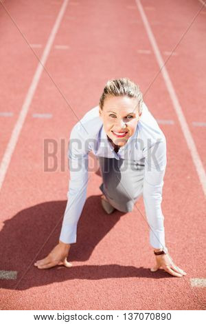 Portrait of businesswoman in ready to run position on running track