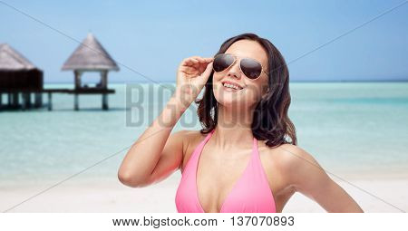 people, fashion, swimwear, summer and travel concept - happy young woman in sunglasses and pink bikini swimsuit over maldives beach with bungalow background