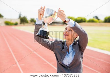 Happy businesswoman holding up a trophy on running track