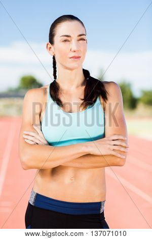 Confident woman standing with arms crossed on running track