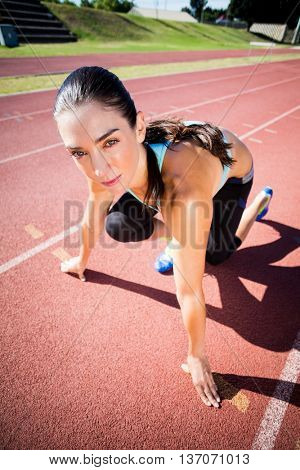 Portrait of female athlete in ready to run position on running track