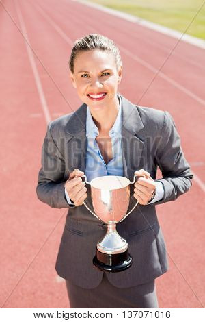 Portrait of happy businesswoman holding a trophy on running track