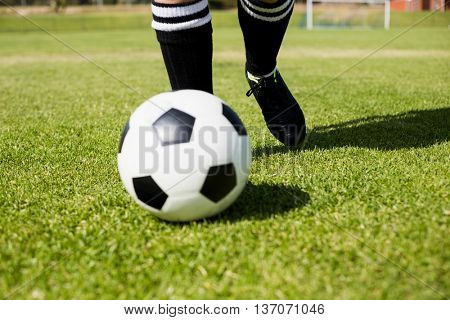 Female football player practicing soccer in stadium