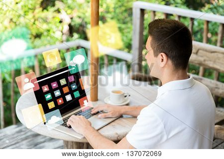 business, people, media and technology concept - close up of businessman with computer menu icons on laptop screen working outdoors on summer terrace and drinking coffee