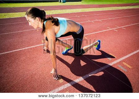Confident female athlete in ready to run position on running track