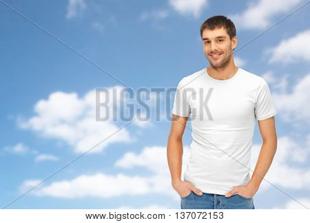 people concept - handsome man in blank white t-shirt over blue sky and clouds background