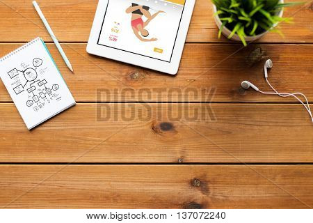 sport, healthy lifestyle and technology concept - close up of tablet pc computer with fitness application on screen, notebook with scheme, pencil and earphones on wooden table