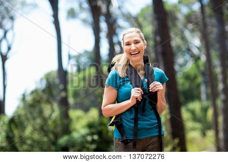 Woman smiling and hiking on the wood
