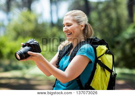 Woman smiling and looking her camera on the wood