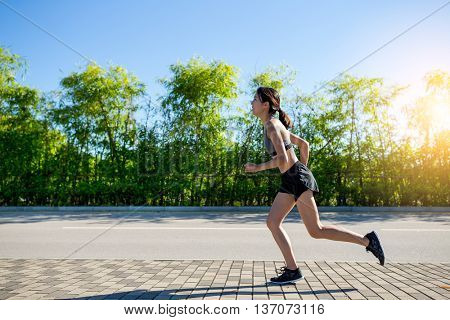Pretty sporty woman jogging at outdoor in sunrise light