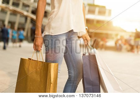 Woman holding shopping bags while walking in a city. Light flare effect