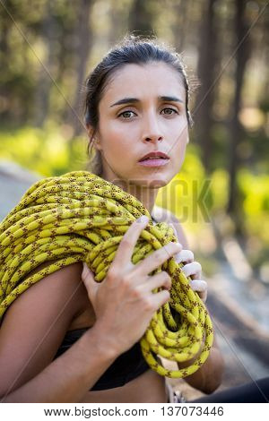 Woman unsmiling and sitting with climbing equipment on the wood