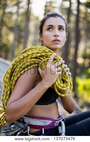 Portrait of woman sitting with climbing equipment on the wood