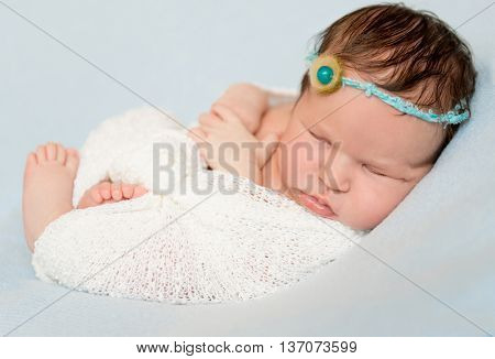 lovely sleeping wrapped baby with bare crossed feet and hands