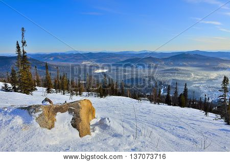 Panoramic winter landscape in the mountains of Western Siberia Russia. Stone ledge on the snowy slopes vast mountain ranges and valleys with pine forest covered and little village - ski resort in the the frosty fog under the mountainside