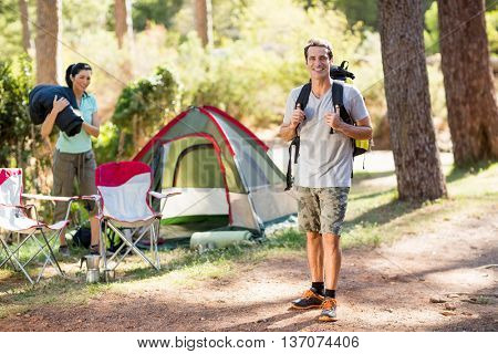 Couple smiling on their camp site on the wood