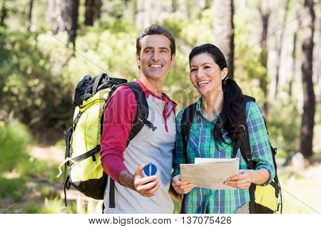 Couple smiling and holding a map and a compass on the wood