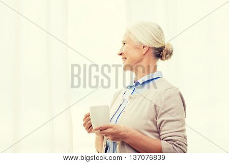 age, drink and people concept - happy smiling senior woman with cup of tea or coffee at home