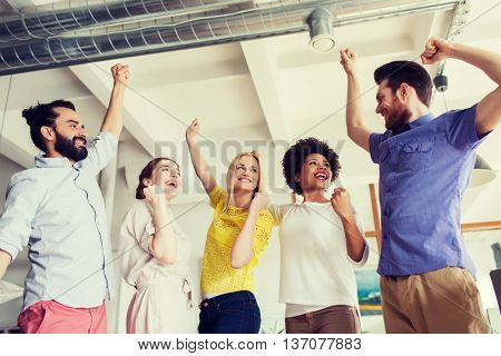 business, triumph, gesture, people and teamwork concept - happy creative team raising hands up and celebrating victory in office
