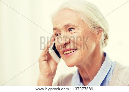 technology, communication age and people concept - happy senior woman with smartphone calling at home