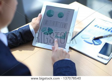 Business person analyzing financial statistics displayed on the tablet screen