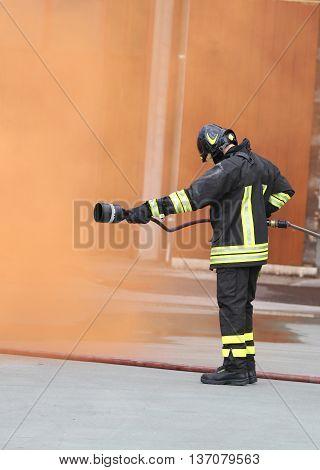 Fireman With An Extinguisher Under The Orange Smoke