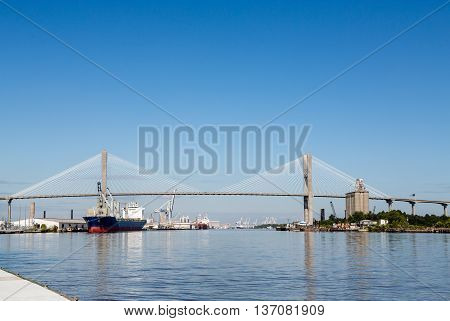 Freight industry at busy harbor on the Savannah River with suspension bridge