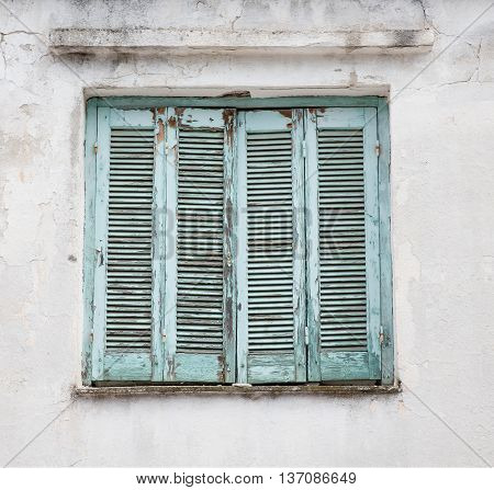 Old worn shutters with peeling blue paint