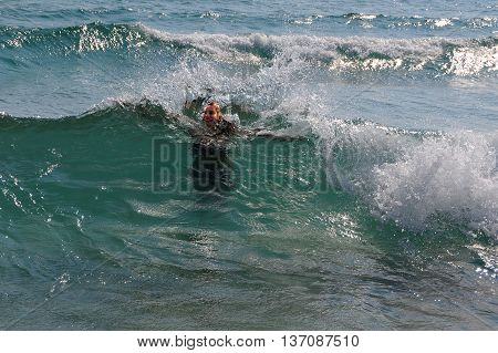 PRIMORSKO BULGARIA - JUNE 30 2016: Young girl in the waves of the Black sea in the summertime