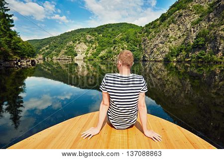 Vacation trip on the river. Handsome man is sitting on the prow of the boat. Vltava river near Prague Czech Republic