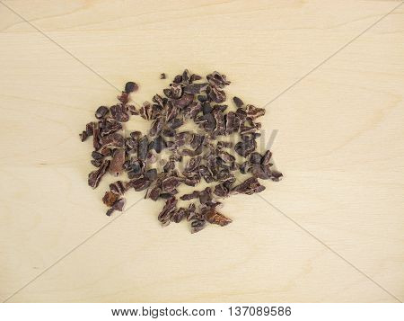 Cocoa nibs from raw cocoa beans on wooden board
