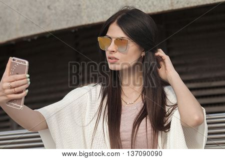 young brunette woman making self portrait using smartphone. girl making selfie. woman in park. Focus on woman. Blurred background.