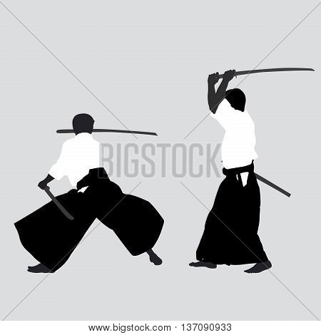 Two men silhouettes with swords practicing Aikido