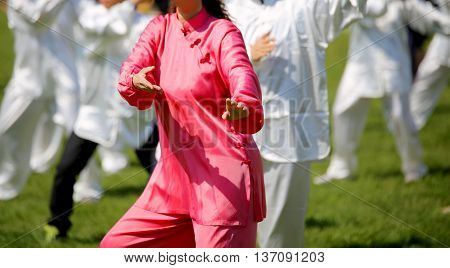 Woman With Pink Silk Dress Perform The Exercises In The Park