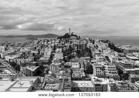 San Francisco, California, USA - April 23, 2016:  Growing clouds over San Francisco Bay, Coit Tower and the North Beach Neighborhood in black and white.