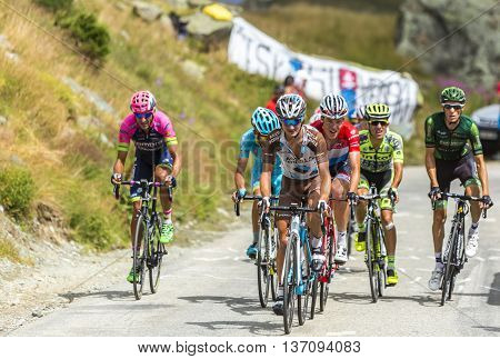 Col de la Croix de Fer France - 25 July 2015: Group of cyclists in the peloton riding in a rocky natural environment at Col de la Croix de Fer in Alps during the stage 20 of Le Tour de France 2015.