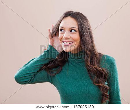 Studio shot portrait of woman who is eavesdropping.
