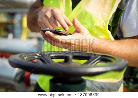 Oil worker using smart phone on the field