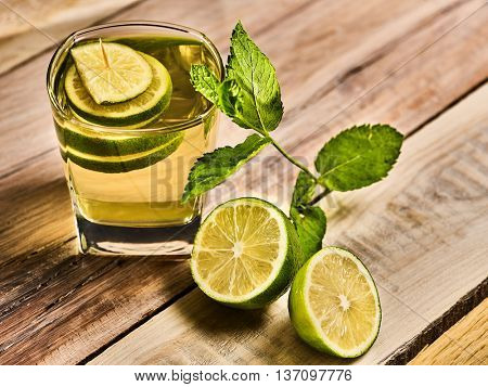 Alcohol drink. On wooden boards is glass with alcohol green transparent drink. A drink number fourteen mojito cocktail with half lime and mint . Top view. Country life. Light background.