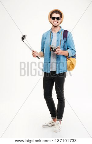 Cheerful young tourist with backpack, old photo camera and smartphone on selfie stick over white background