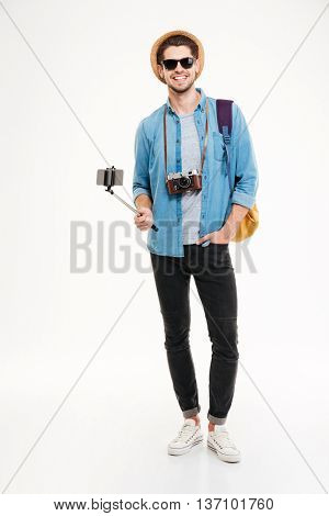 Happy young tourist holding backpack, vintage camera and smartphone on selfie stick over white background